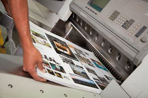printing press operator moving brochures in production