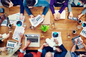 eight people photographed from above with laptops, coffee and business charts