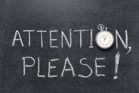 "attention please written on blackboard with stopwatch as letter ""o"""