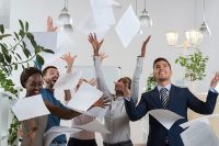 five business people smiling as papers float in air in bright office