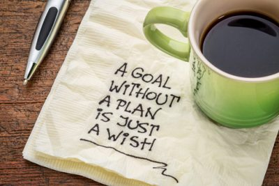 "cup of coffee sitting on a napkin printed with ""a goal without a plan is just a wish"""
