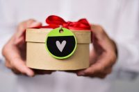 holding gift box with a heart tag